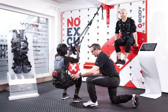 Mann und Frau führen unter Anleitung EMS-Übungen durch